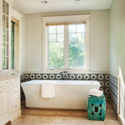 Stand alone bathtub under window with garden view