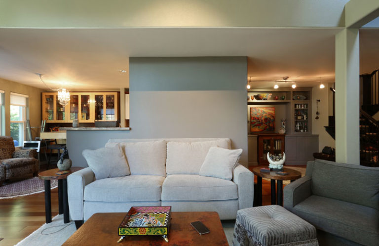 Grey couch with two grey pillows in front of wooden table