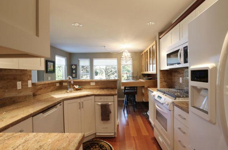 White kitchen cabinets next to the white fridge