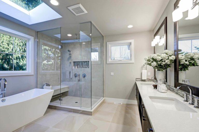 Glass shower panel next to the white bathtub