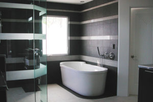 White stand alone bath tub inside of the dark tiled bathroom