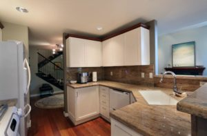 White hanging kitchen cabinets above marble countertop