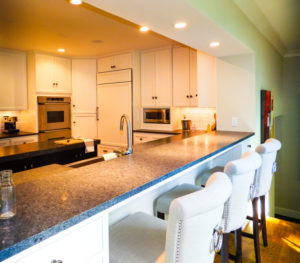 White chairs next to the white kitchen cabinets