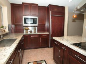 Brown wooden kitchen cabinets wth marble countertop