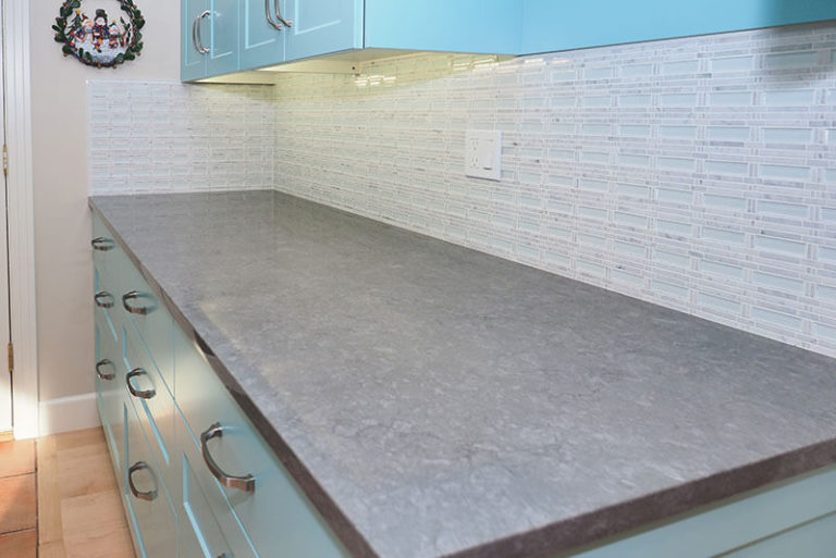 Grey stone countertop on blue kitchen cabinet