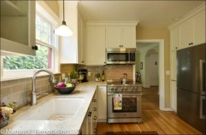 A new kitchen with white cabinets and crown molding closing the gap up to the ceiling. Stainless steel appliances and light marble countertops.