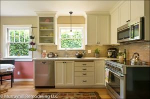 A newly remodeled kitchen with white cabinets and one has a glass front allowing you to see the plates and bowls inside.