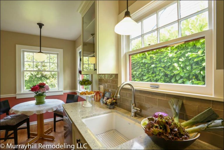 A panoramic shot of the wide window above the sink with green shrubs outside and the sun shining in.