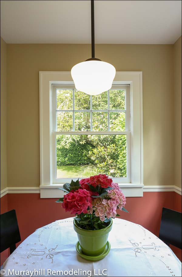 A centered shot of the dining room table which is topped with a white table cloth and a vase of red and pink roses.