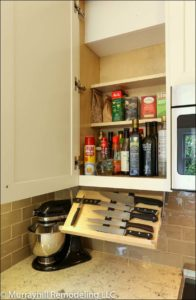 A pull down knife holder that hides underneath the upper cabinet above the countertop.