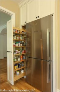 A slide out 5 foot built-in spice rack pulled out next to the stainless steel fridge.