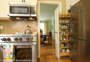 A view of the slide out 5 foot spice rack and the gas range with the stainless steel microwave above it.