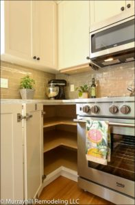 A view of the inside of the large corner cabinet with a 3-piece folding corner door next to a stainless steel gas range.