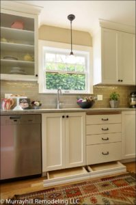 Slide out hidden drawers on the bottom of the sink base cabinet that are faced with the baseboard so when they are closed you can't tell they are there.